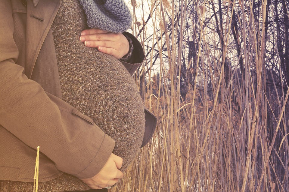 heavily pregnant woman in autumn setting